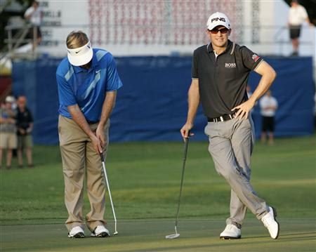 Russell Henley of the U.S. (L) practices his putt swing as Scott Langley waits to putt on the 18th green during the third round of the Sony Open golf tournament in Honolulu, Hawaii January 12, 2013. REUTERS/Hugh Gentry