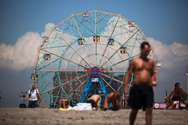 People at Coney Island in the Brooklyn borough of New York experience sunny weather while Hurricane Irene bears down on the eastern seaboard further south on Friday, Aug. 26, 2011. The low number of visitors at the typically crowded beach reflects the wind, rain, and flooding dangers the storm poses to the already saturated New York state. (AP Photo/John Minchillo)