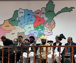 Members of the loya jirga listen during the first of …