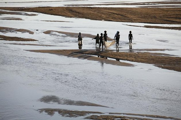 Des enfants jouent et s'apprêtent à pêcher sur les berges d'une rivière asséchée, près de l'autoroute Bauchi-Gombe, au Nigeria. Selon le Bureau de coordination des affaires humanitaires de l'Onu, malgré les pluies et de meilleures récoltes, seize millions d'Africains sont menacés de disette l'an prochain dans l'arc sahélien en raison des conflits et de la croissance rapide de la population dans cette région. /Photo prise le 28 novembre 2013/REUTERS/Afolabi Sotunde