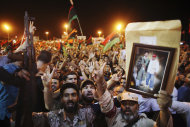 People celebrate the capture in Tripoli of Moammar Gadhafi's son and one-time heir apparent, Seif al-Islam, at the rebel-held town of Benghazi, Libya, early Monday, Aug. 22, 2011. Libyan rebels raced into Tripoli Sunday and met little resistance as Gadhafi's defenders melted away and his 42-year rule rapidly crumbled. (AP Photo/Alexandre Meneghini)