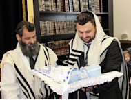 In this photo provided by the Furer family Rabbi Abraham Dauss, left, and Moishe Furer, a rabbinical student in Berlin holding his son Elchanan attend a circumcision ceremony in Berlin, Germany, Friday, June 29, 2012. Elchanan was born five days before a regional court in Cologne ruled in June that the practice of circumcision amounted to causing bodily harm to a child. Though the Cologne court's decision has raised fears among Muslims and Jews that circumcising their children could get them into legal trouble, it has had little practical effect in reducing religious circumcisions _ especially since the government has weighed in with assurances to both communities that their practices will be respected. (AP Photo/Aviel Granov)