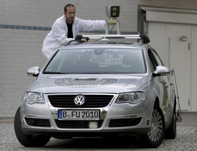 In this  Friday, Sept. 16, 2011 photo Autonomos Labs assistant Paul Czerwionka touches a 360 degree laser scanner on top of a car Berlin, Germany. The car is driven by a computer that steers, starts a