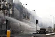 Firefighters spray water onto buildings set on fire by rioters the night before in Croydon, south London, Tuesday, Aug. 9, 2011. A wave of violence and looting raged across London and spread to three other major British cities Tuesday, as authorities struggled to contain the country's worst unrest since race riots set the capital ablaze in the 1980s. (AP Photo/Sang Tan)