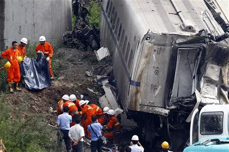 Rescuers carry a body of a victim discovered among the wreckage after two carriages from a bullet train derailed and fell off a bridge in Wenzhou