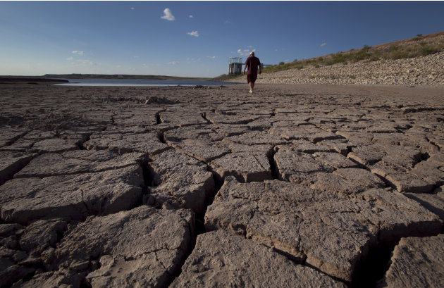 FILE - In this Aug. 7, 2011 file photo, Eddie Ray Roberts, superintendent of the city's waste and water department walks on the dried bed of Lake E.V. Spence in Robert Lee, Texas. After years of dimin