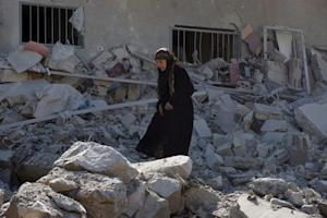 A woman makes her way through the rubble of damaged …
