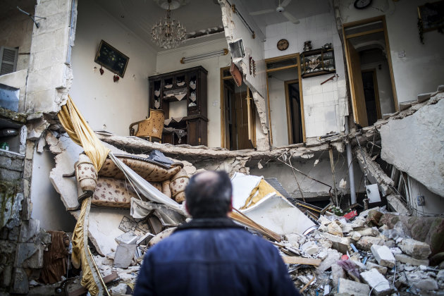 A civilian looks at a destroyed home in Aleppo, Syria, Thursday, Jan. 3, 2013. The area is immersed in a Syrian civil war that the United Nations estimates has killed more than 60,000 people since the revolt against President Bashar Assad began in March 2011. (AP Photo/Andoni Lubaki)