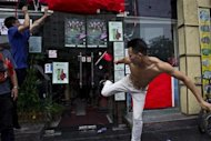 A man kicks the door of a Japanese pub decorated with Chinese national flags during a protest on the 81st anniversary of Japan's invasion of China, in Shenzhen, September 18, 2012. REUTERS/Keita Van