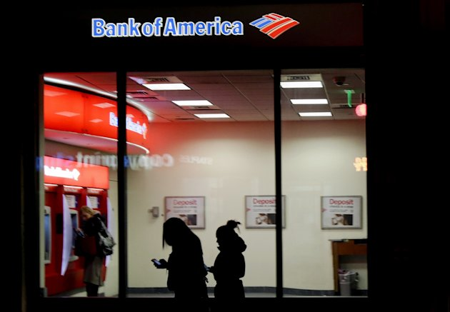 In this Thursday, Dec. 13, 2012 photo people use a Bank of America ATM in Boston. Banks including JPMorgan Chase, U.S. Bancorp and Bank of America seized on government payments for unemployment compensation as a business opportunity and pitched card programs to many states. However to cover the costs of the programs, banks have hit all card users with a plethora of new fees. (AP Photo/Charles Krupa)
