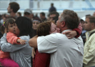 A relative embraces a survivor upon the arrival of the Arabella riverboat with dozens of survivors of a shipwreck in Kazan, on Sunday, July 10, 2011, on the Volga River, in central Russia. A woman drowned and some 100 remain missing after the double-decker passenger boat sank in the middle of the river some 3 kilometers (2 miles) away from the nearest bank, in the Tatarstan region, about 450 miles (750 kilometers) east of Moscow. (AP Photo/Roman Kruchinin)