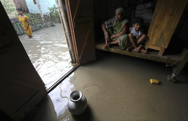 Flood-affected residents sit inside their flooded house at Dhuhibala village