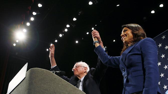 Democratic presidential candidate Bernie Sanders clasps hands with Hawaii Representative Tulsi Gabbard at the start of a campaign rally in Raleigh