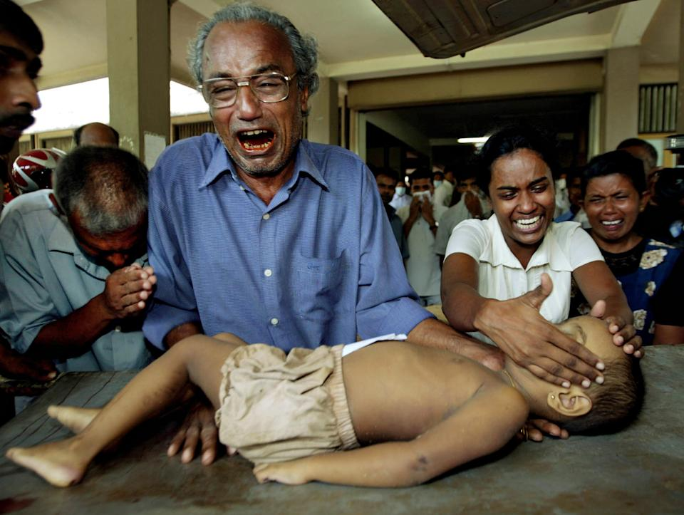 FILE - In this Dec. 27, 2004 file photo, a young tsunami victim's father cries as he holds the body of his son along with other family members at ...