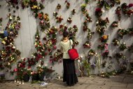 A woman is seen in front of wall decorated with flowers in memory of the victims of Friday's bomb attack and shooting rampage in Oslo, Norway, Tuesday, July 26, 2011. The defense lawyer for Anders Behring Breivik said Tuesday his client's case suggests he is insane, adding that someone has to take the job of defending him but that he will not take instructions from his client. Geir Lippestad told reporters that the suspect in the bombing on the capital and the brutal attack on a youth camp that killed at least 76 people is not aware of the death toll or of the public's response to the massacre that has rocked the country. (AP Photo/Emilio Morenatti)