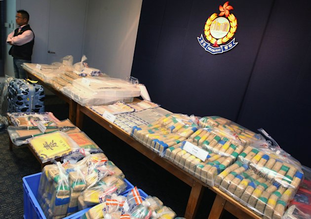 A Hong Kong police officer stands by packages of cocaine worth about $600 million Hong Kong dollars (US$77 million) which were found at a warehouse in Hong Kong during a news conference Sunday, Sept.