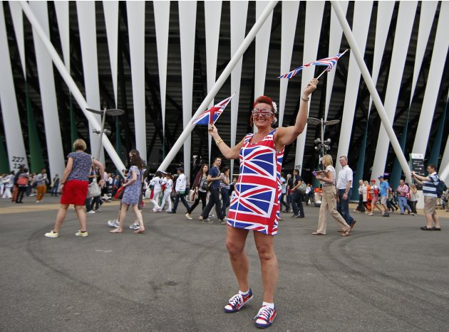 A fan waves Union Jack flags as she arrives for the opening ceremony of the London 2012 Olympic Games at the Olympic Stadium