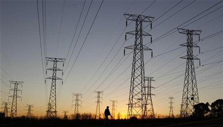 A man walks past electricity pylons as he returns from work in Soweto, outside Johannesburg May 15, 2012. REUTERS/Siphiwe Sibeko
