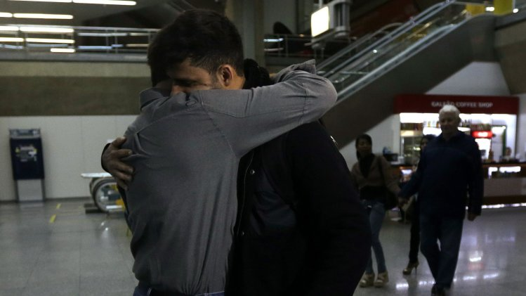 U.S. journalist Greenwald embraces his partner Miranda upon his arrival at Rio de Janeiro's International Airport