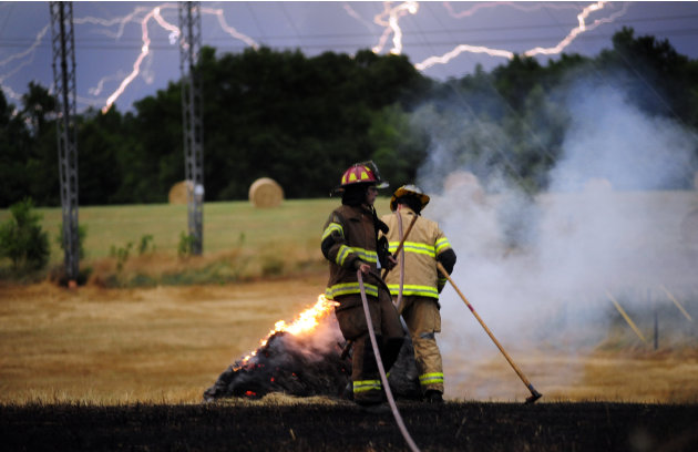 Lightning streaks across the sky while Athens-Clarke Firefighters work to extinguish a hay fire that was caused by a lightning strike, Thursday, May 26, 2011, in Athens, Ga. Firefighters responded to