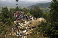 Nepalese rescue workers and civilians gather around the wreckage of a Beechcraft 1900D operated by Buddha Air after it crashed in the mountains outside Bisankunarayan village, just south of Katmandu, Nepal, early Sunday, Sept. 25, 2011. The plane carrying tourists to view Mount Everest crashed while attempting to land in dense fog on Sunday, killing all 19 people on board, officials said. (AP Photo/Niranjan Shrestha)