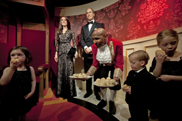 Child models eat scones as they pose with waxworks of Britain's Royal couple William and Catherine, the Duke and Duchess of Cambridge, at Madame Tussauds in Amsterdam, Netherlands, Wednesday, April 4,