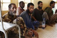 Radical Islamists arrested by French and Malian authorities in Timbuktu region sit in handcuffs in the military police headquarters in Gao, Mali, in this February 26, 2013 file photo. REUTERS/Joe Penney/Files