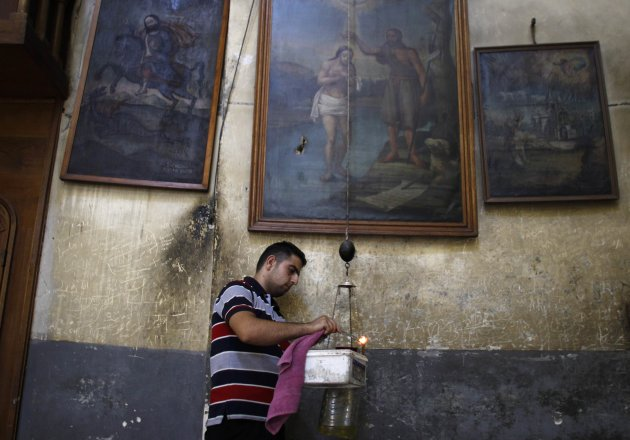 An employee of the Church of the Nativity, lights a candle in Bethlehem