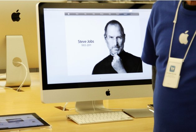 The homepage of apple.com showing the obituary of ex-Apple CEO Steve Jobs is displayed on an iMac at an Apple Store in Glendale