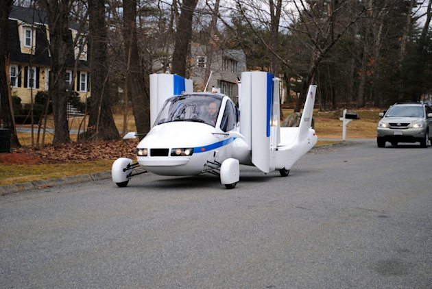 In this undated photo provided by Terrafugia Inc., the company's prototype flying car, dubbed the Transition, travels down a street with its wings folded.  The vehicle has two seats, four wheels and w