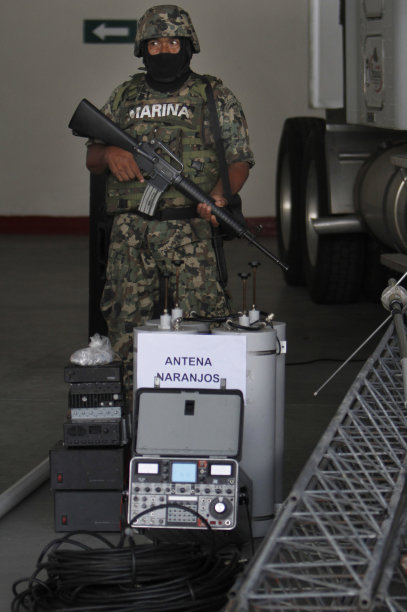 A member of the Mexican Navy stands next to seized telecommunications equipment, allegedly built by the Zetas drug cartel, during a media presentation in Veracruz, Mexico, Thursday Sept. 8, 2011. The Mexican Navy says it has dismantled a telecommunications system set up by the cartel and has arrested 80 people, including six policemen. (AP Photo/Marco Ugarte)