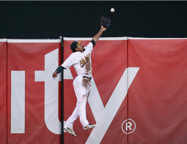 Oakland Athletics center fielder Coco Crisp prevents Detroit Tigers first baseman Prince Fielder from gaining a second inning home run with a catch at the wall during Game 3 in their MLB ALDS playoff