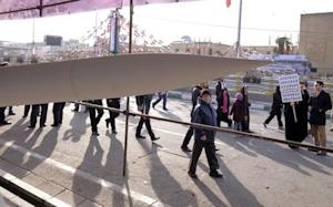 People walk near an Iranian-made missile during a ceremony…