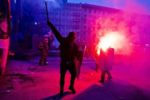 A protester swings a baton towards a burning police …