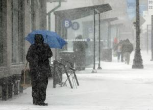 A passenger waits in the snow to board a bus at Kennedy…