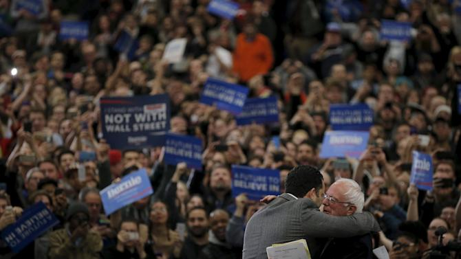 Democratic U.S. presidential candidate Bernie Sanders is hugged as he arrives to speak at a campaign rally in Warren, Michigan