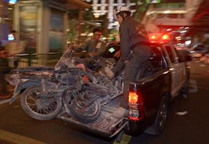 Thai rescue workers transport damaged motorcycles from…
