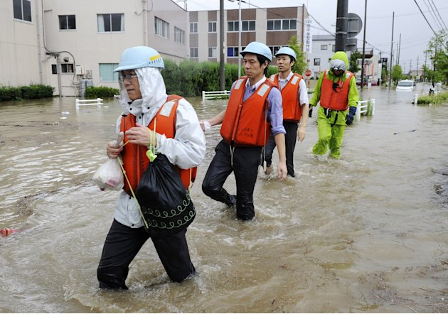 Local residents wade through a flooded street caused by approaching typhoon in Nagoya, central Japan,  Tuesday, Sept. 20, 2011. Thousands of people in central Japan have been advised to evacuate as th