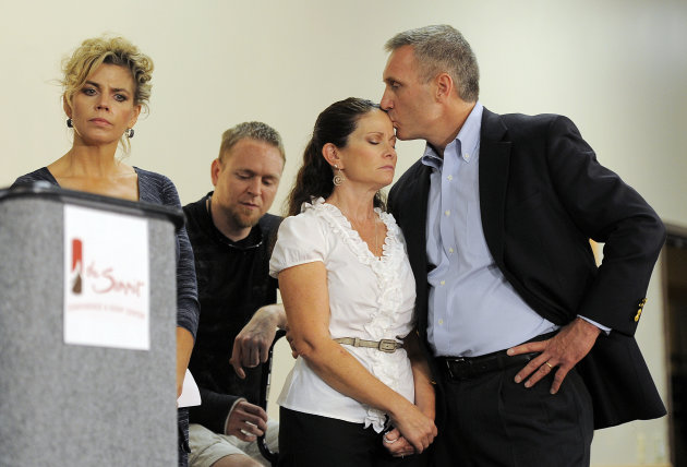 Thomas Teves, right, kisses his wife Caren Teves, center, at a press conference by families of victims of the Colorado theater shooting, in Aurora, Colo., on Tuesday, Aug. 28, 2012. Thomas and Caren Teves lost their son Alexander Teves, 24, in the shooting. Families of some of the 12 people killed in the Colorado theater shooting are upset with the way the millions of dollars raised since the tragedy are being distributed.   (AP Photo/Chris Schneider)