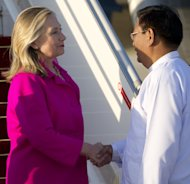 US Secretary of State Hillary Rodham Clinton, left, is greeted by Myanmar Deputy Foreign Minister Myo Myint upon her arrival by her airplane in Naypyidaw, Myanmar, Wednesday, Nov. 30, 2011. Making a diplomatically risky trip to the long-isolated Southeast Asian nation of Myanmar, Clinton said she wanted to see for herself whether new civilian leaders are truly ready to throw off 50 years of military dictatorship _ a test that includes rare face-to-face meetings with former members of the junta whose brutal rule made a poor pariah state of one of the region's most resource-rich nations. (AP Photo/Saul Loeb, Pool)