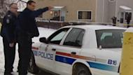 Police stand outside the north Edmonton townhouse where the bodies of two boys were found on Dec. 20.