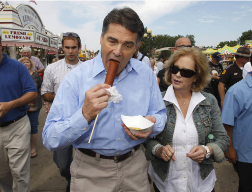 Republican presidential candidate, Texas Gov. Rick Perry walks with his wife Anita and eats a veggie corn dog as they visited the Iowa State Fair in Des Moines, Iowa, Monday, Aug. 15, 2011. (AP Photo/Charles Dharapak)