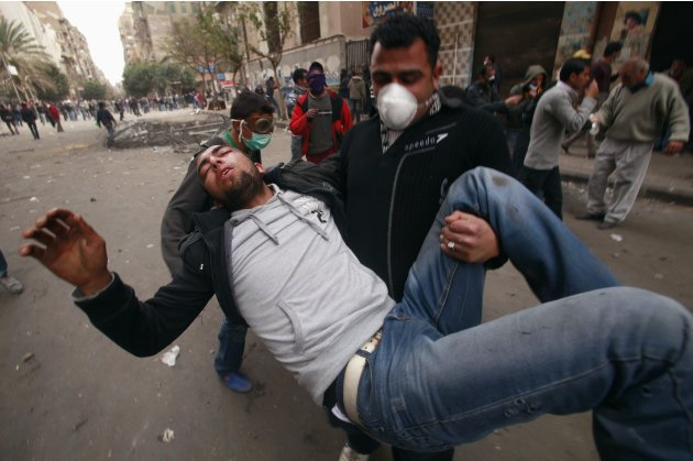 A wounded protester is carried during clashes with security forces near the Interior Ministry in Cairo