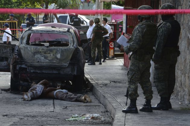 GRAPHIC CONTENT - In this Sept. 26, 2011 photo, Mexican Army soldiers look at two bodies lying next to a charred vehicle in the Pacific resort city of Acapulco, Mexico. Acapulco has seen a surge of cr