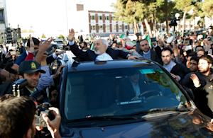 Iranian Foreign Minister Mohammad Javad Zarif (C) gets …