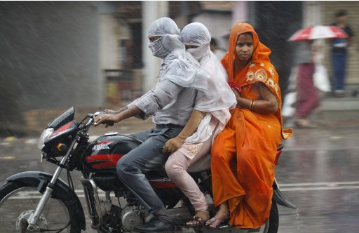 A man along with his family rides a motorcycle during a heavy rain shower in Allahabad