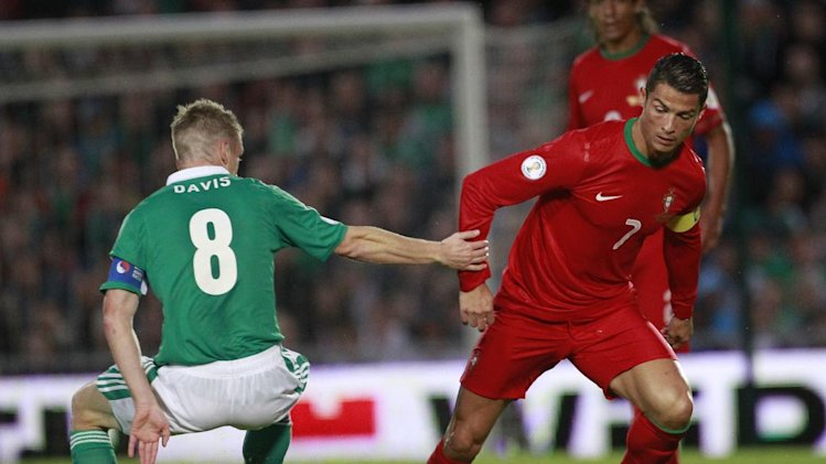 Portugal's Cristiano Ronaldo, right, wins the ball from Northern Ireland's Steven Davis during their World Cup Group F qualifier soccer match at Windsor Park, Belfast, Northern Ireland, Friday, Sept. 6, 2013. (AP Photo/Peter Morrison)