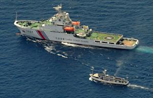 A China Coast Guard ship (top) and a Philippine supply …