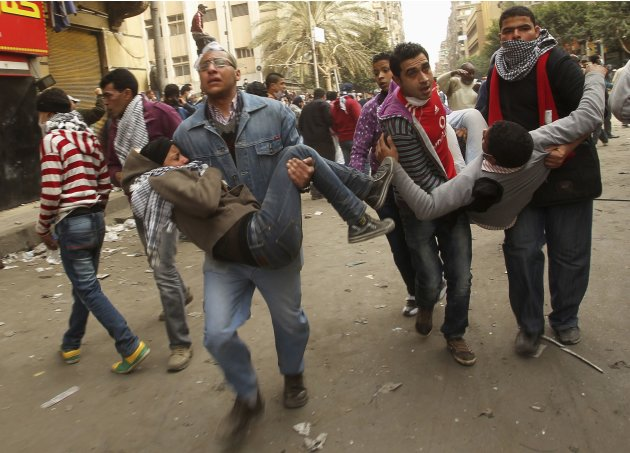 Wounded protesters are evacuated during clashes with security forces near the Interior Ministry in Cairo