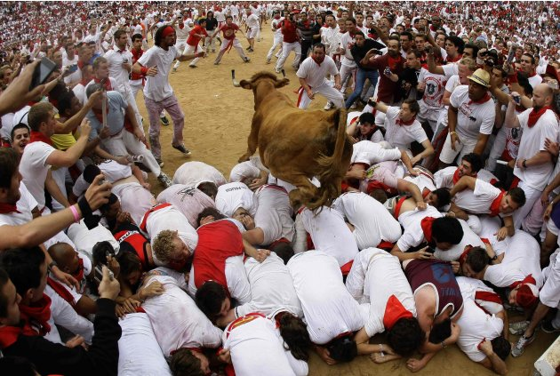 A wild cow leaps over a group of revellers following the second day of the running of the bulls at the bullring during the San Fermin festival in Pamplona